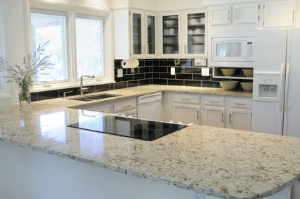 Modern clean white kitchen with shiny stone worsurfaces, induction hob , sink and kitchen cabinets