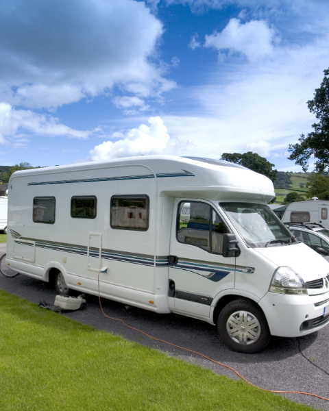 White motorhome against a blue sky with grass in the foreground