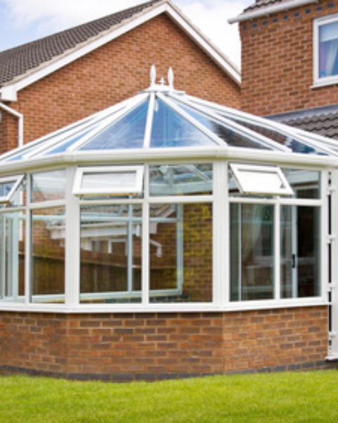 A pentagon shaped conservatory with white UPVC frame and glass roof connected to a house