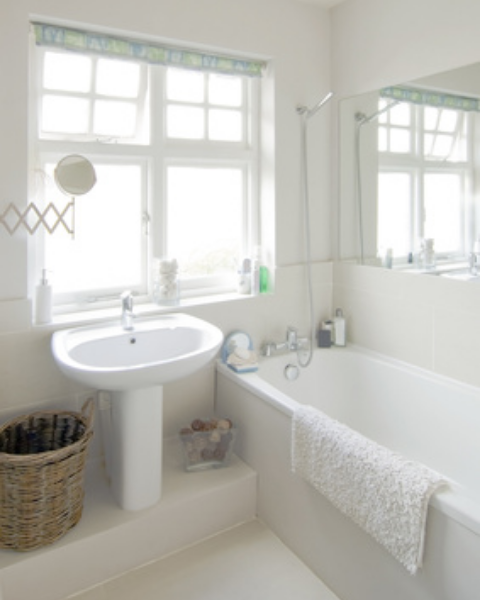A clean white bathroom with pedestal sink, bathtub and shower attachment